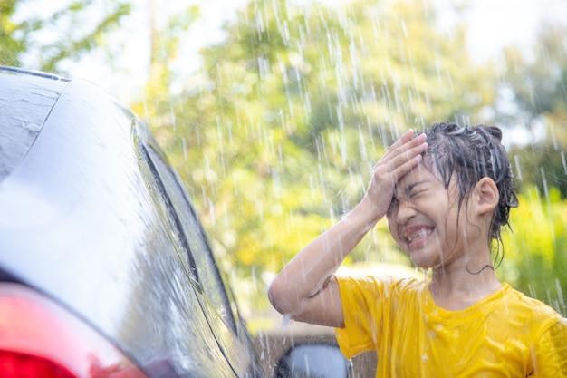 家で水しぶきと日光で車を洗う幸せなアジアの女の子