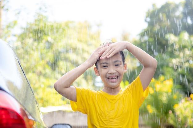 집에서 물이 튀고 햇빛에 차를 씻는 행복한 아시아 소녀