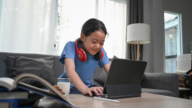 Happy asian girl watching cartoons online on digital tablet while sitting on sofa.