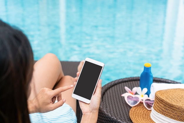 Happy asian girl wearing swimsuit lying on sunbed and using smart phone relaxing at the poolside with hat