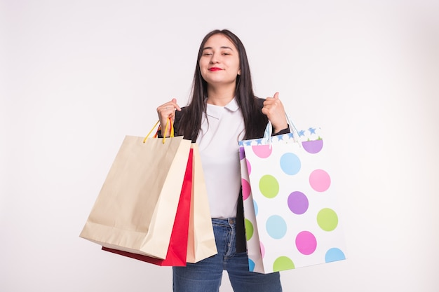 Happy asian girl with red lips holding shopping bags on white
