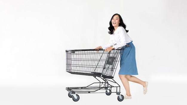 Happy asian girl with shopping cart on white isolated wall