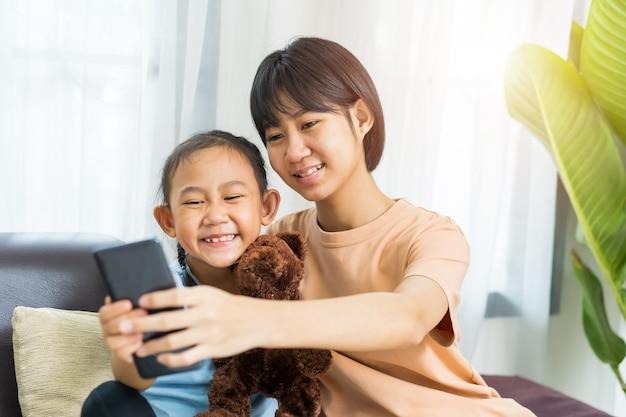 妹と幸せなアジアの女の子が自宅で一緒にスマートフォンで遊ぶ