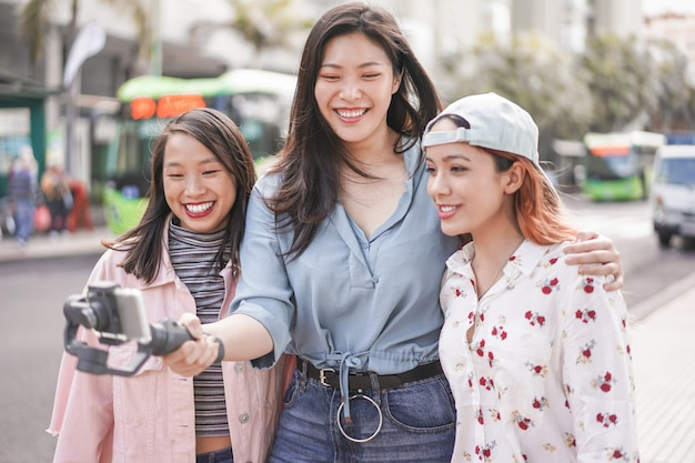 Happy asian girls making vlog video at bus station. trendy friends blogging for social media outdoor