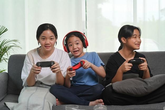 Счастливые азиатские девушки сидят вместе на диване у себя дома и играют в видеоигры