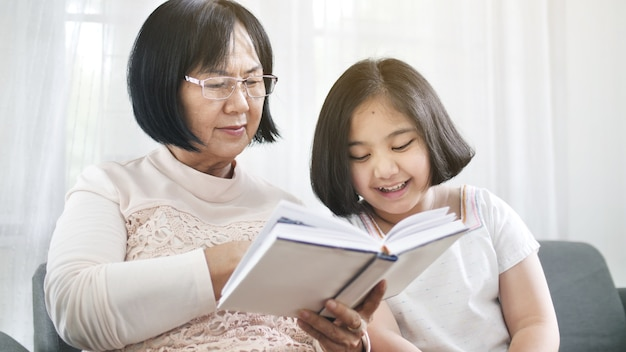Happy asian grandmother and lovely girl reading book together at home