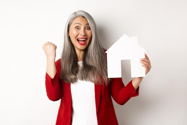 Счастливая азиатская бабушка показывает вырез бумажного домика и жест насоса кулака, кричит да от радости, покупая недвижимость, стоя на белом фоне.