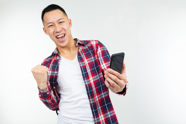 Happy asian guy won a prize while holding a smartphone on a white background.