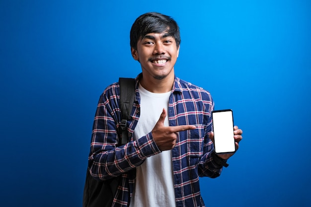 플란넬 셔츠를 입고 파란색 배경에 빈 스마트폰 화면을 가리키고 있는 행복한 아시아 미남 학생. 남자는 충격과 놀란 표정을 보여줍니다.