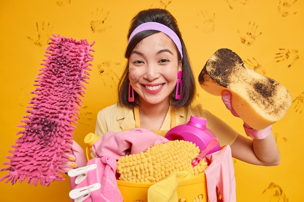 Happy asian housemaid being tired but satisfied with results of her work wears headband rubber gloves holds sponge wipes dust uses mop for washing floor stands near basket full of untidy laundry