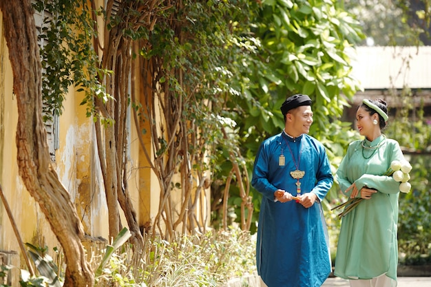 通りを歩いて式典の後にお互いを見ているアオザイのドレスを着た幸せなアジアの夫と妻