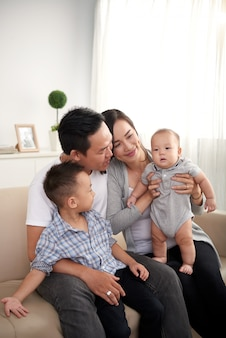 Happy asian husband, wife and two kids sitting on couch at home