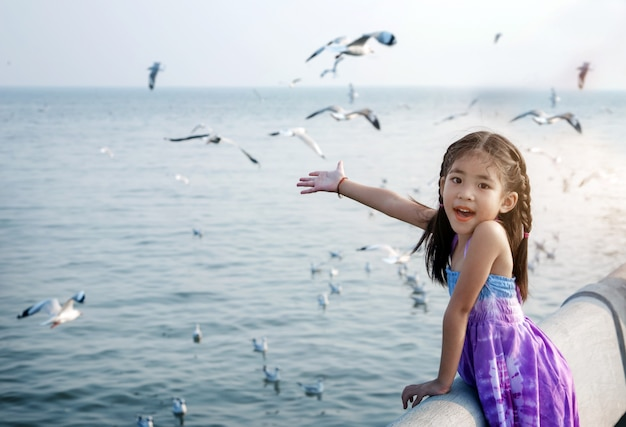 Happy asian kid like wind and bird on seascape
