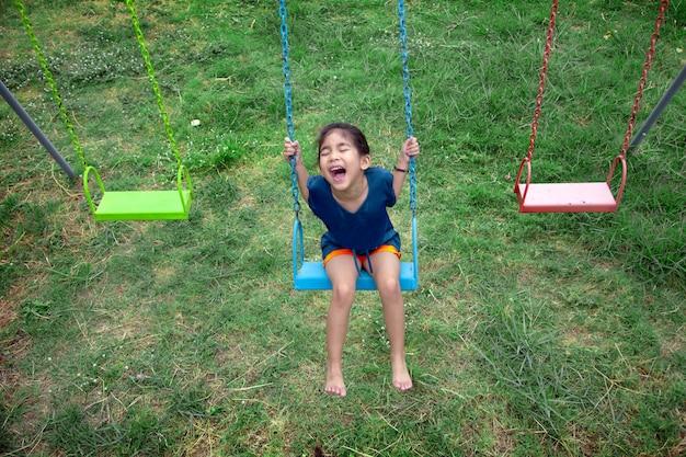 Happy asian kid play swing outdoor playpark