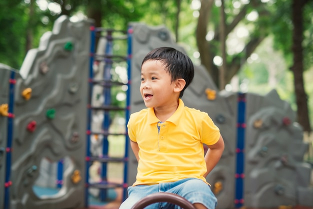 Happy asian kid playing seesaw playground. cute boy child excercise on equipment to playful and joyful. he smile show happy and funny to play in plublic playground for children in comunity.