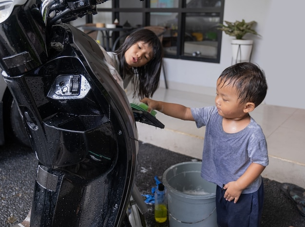 Happy asian kid playing and washing motorbike scooter at home