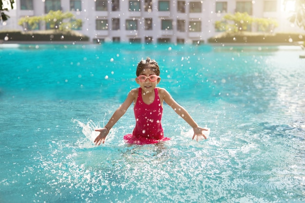 Happy asian kid playing water in swimming pool