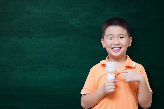 Happy asian kid smiling on empty green chalkboard