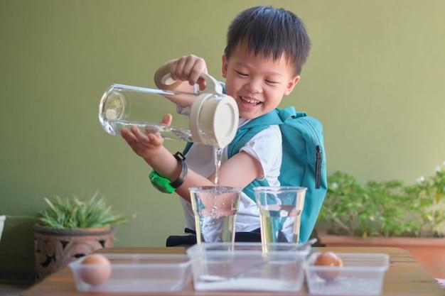 楽しくて簡単な浮遊卵科学実験を行うために水を注ぐ科学を勉強している幸せなアジアの子供