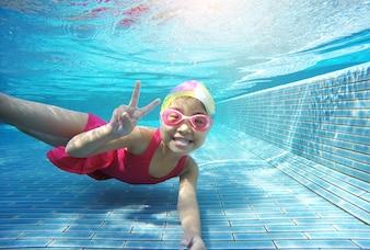 Happy asian kid swimming underwater in summer