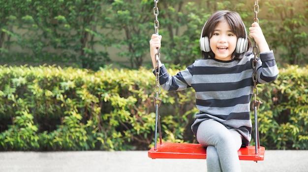 Счастливый азиатский ребенок слушает музыку с беспроводным наушником и играет на качелях в парке kidtergarden с цифровым стилем жизни на горизонтали