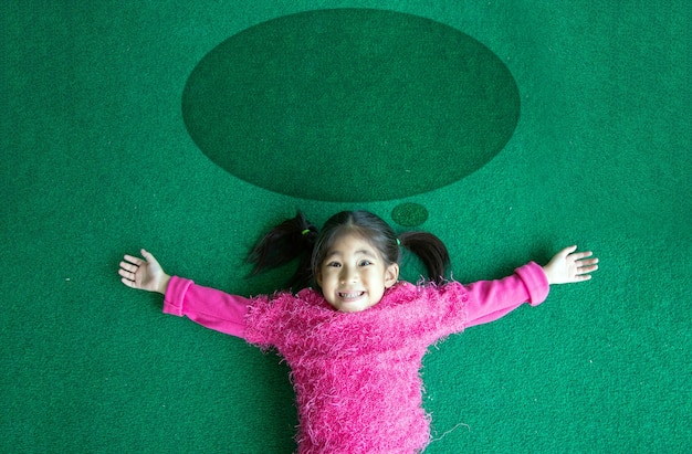 幸せなアジアの子供たちは緑の草と中のアイデアのような円の形に手を開きます