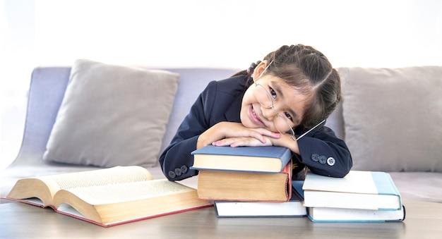 バナーサイズのソファで自宅で学ぶために本を読んで幸せなアジアの子供たち