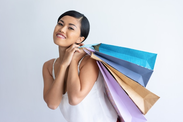 Happy asian lady carrying heap of shopping bags