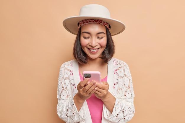 黒髪の幸せなアジアの女性は帽子をかぶって、白いコートはスマートフォンの画面で喜んで見えますテキストメッセージはベージュの壁に立ち向かいますダウンロード新しいアプリケーション
