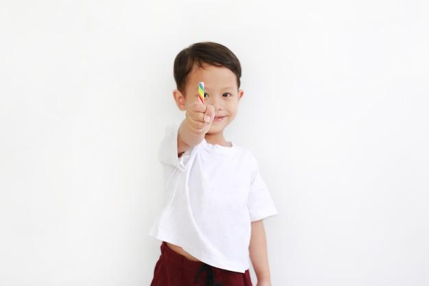 흰색 배경에 롤리팝 사탕을 들고 행복 한 아시아 어린 소년. 그의 손에 있는 다채로운 사탕 막대에 초점