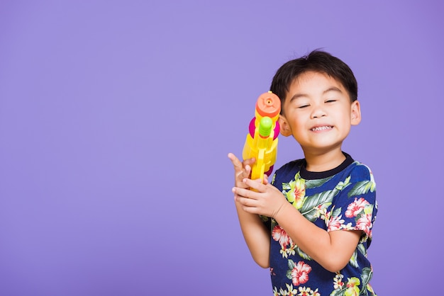 Happy asian little boy holding plastic water gun, thailand songkran festival day