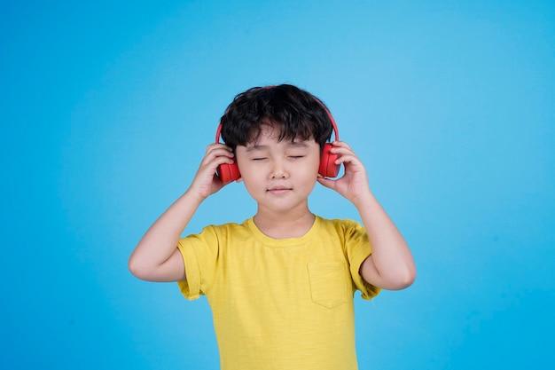 Счастливый азиатский маленький мальчик с наушниками слушает музыку