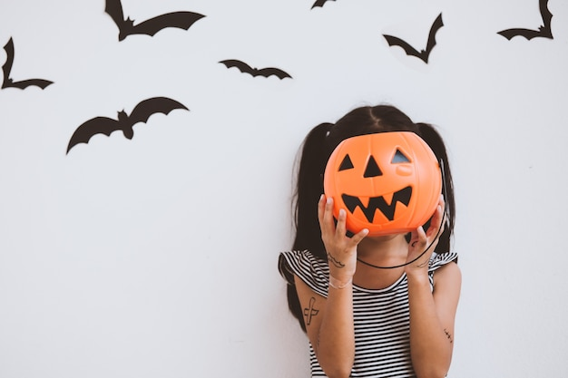 Happy asian little child girl in costumes and makeup having fun on halloween celebration