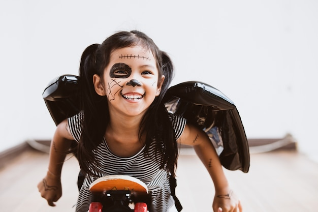 Happy asian little child girl in costumes and makeup having fun to play with roller board