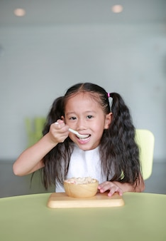 Happy asian little child girl eating healthy food with deliciousness at home.