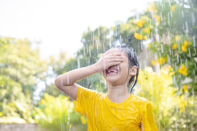 햇빛 속에서 비와 함께 즐겁게 노는 행복한 아시아 어린 소녀