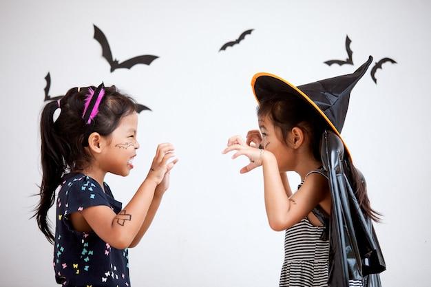 幸せなアジアの小さな子供の衣装や化粧のハロウィーンのお祝いに楽しんで