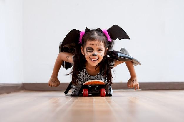 幸せなアジアの小さな子供の女の子の衣装やメイクの遊びに遊ぶローラーボード