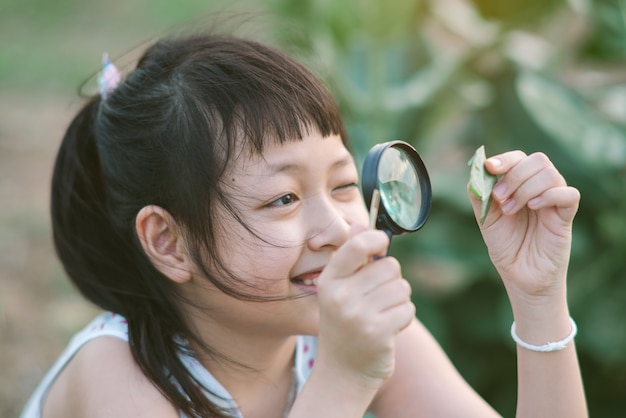 Happy asian little child girl looking through a magnifying glass on green leaf tree in the park