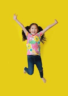 黄色の背景に分離された空気で花柄夏ドレスジャンプと自由運動を身に着けている幸せなアジアの小さな子供女の子。