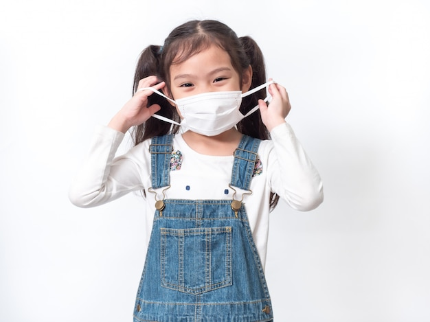 Happy asian little cute girl 6 years old wearing a hygienic mask to protective spread the coronavirus or covid-19 on white wall.