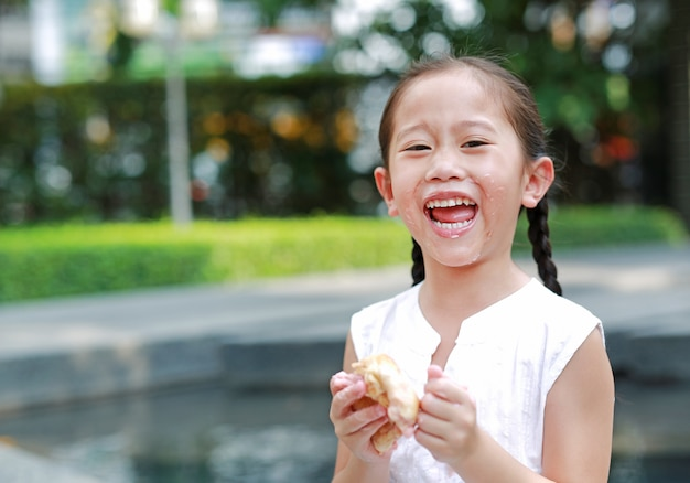 Happy asian little girl eating bread with stuffed strawberry