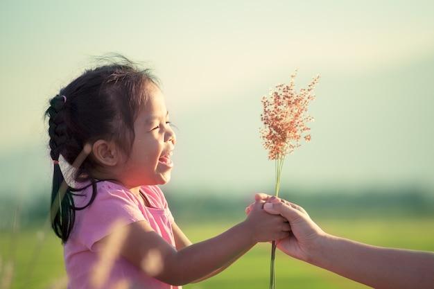Счастливый азии девочка, давая трава цветок ее мать с любовью в старинный оттенок