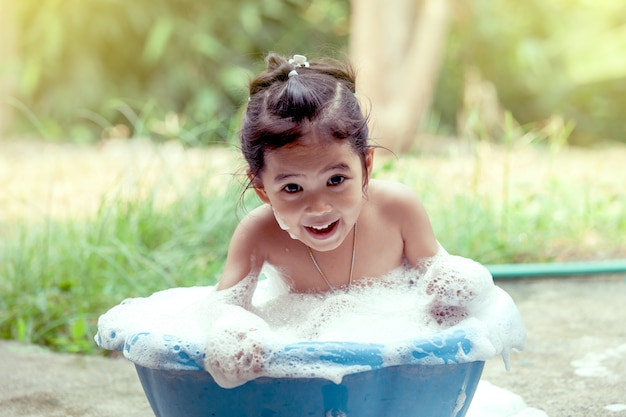 Happy asian little girl having fun and playing with foam