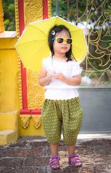 寺院のサングラスと傘でタイの時代のドレスで幸せなアジアの少女