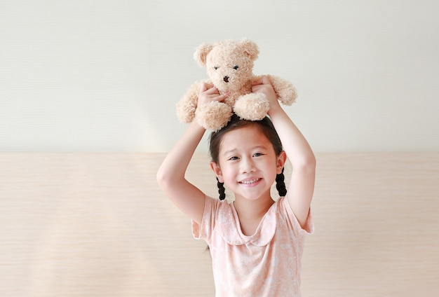 Happy asian little girl picking up brown teddy bears on her head while sitting on the bed at home