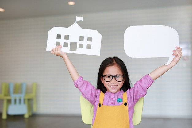Happy asian little girl in pink-yellow dungarees holding mock-up paper school and empty blank speech bubble to tell something in classroom with looking straight. education and conversation concept.
