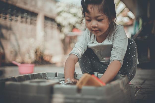Счастливая азиатская маленькая девочка грязно играет с пластиковой игрушкой на открытом воздухе