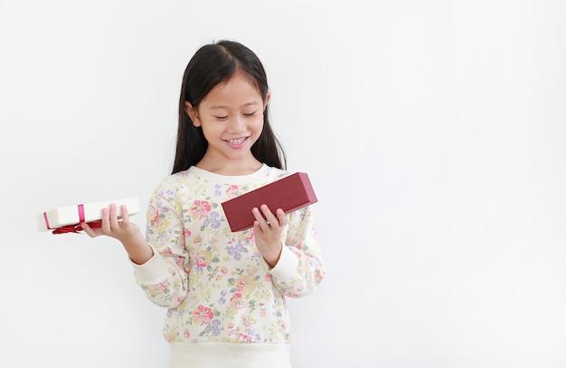 Счастливая азиатская маленькая девочка, открытая подарочная коробка, концепция с новым годом и рождеством