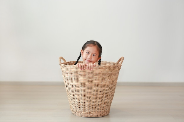 Happy asian little kid girl sitting in rattan basket in room at home